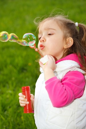Portrait of a cute girl blowing soap bubbles photo