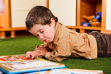 Preschool boy reading a large book Stock Photo - 6899115