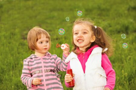 Two lovely girls blowing bubbles photo