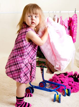 A toddler girl putting clothing into trolley photo