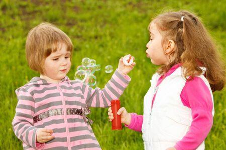 Two cute friends blowing soap bubbles photo
