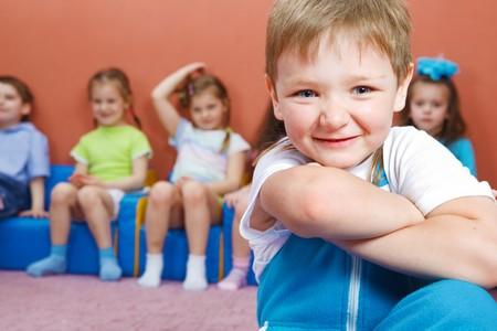 escuela primaria: Niños sentados en sillas, niño preescolar en frente de ellos