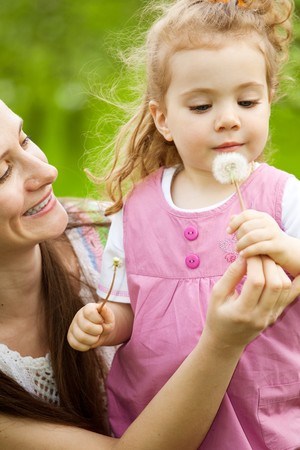 Mom giving a white dandelion to daughter photo
