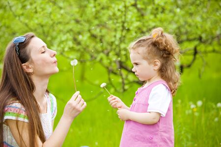 Mother and curly girl blowing dandelion away Stock Photo - 7001568