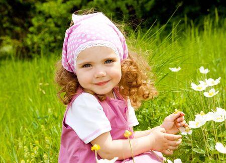 jolie petite fille: Sourire de jeune fille sur le pr� cherchant � droite � la cam�ra