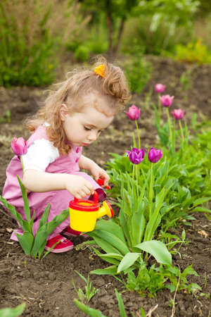 Cute curly girl watering flowers in the garden Stock Photo - 7001585