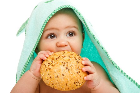 Closeup portrait of a baby eating seeded bun photo