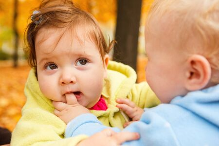 A sweet baby girl biting her friends finger photo