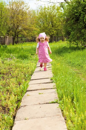 Sweet curly girl  running along the path photo