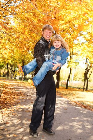 Daddy and daughter playing in the autumn park photo