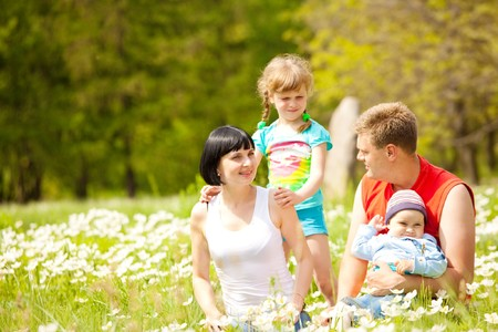 Lovely happy family enjoying time on the meadow photo