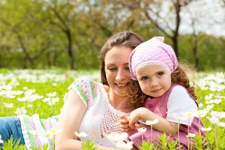 Happy mother and daughter among white flowers Stock Photo - 7020846