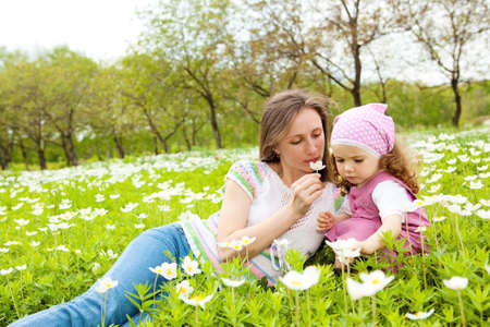 Mother and daughter smelling flower and enoying time together photo