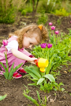 Cute curly girl watering flowers in the garden Stock Photo - 7020911