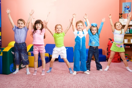 preschool children: Several joyful kids with their hands up