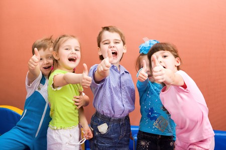 excited people: Group of happy kids showing their thumbs up Stock Photo