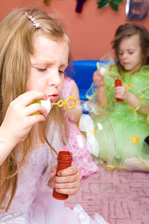 Preschool girl blowing a large bubble at the birthday party Stock Photo - 7020903