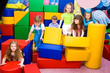 Group of joyful kids playing with large leather blocks Stock fotó