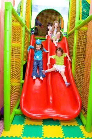 Four preschool girls sliding down