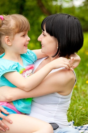 Mother and daughter sitting at the river bank Stock Photo - 7020908