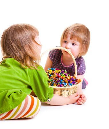 Cute girls holding  basket full with candies photo