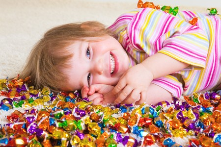 A sweet laughing kid lying among candies photo