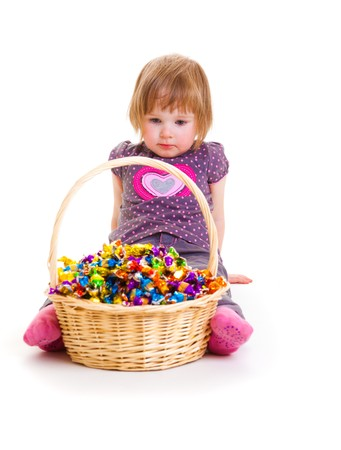 Sweet baby looking at the basket fulll with candies Stock Photo - 7021068