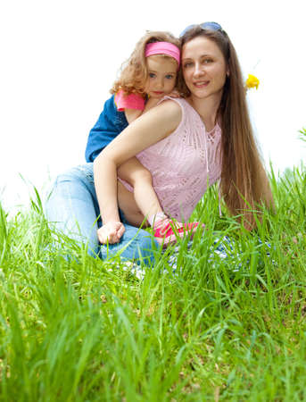 Cheerful mother and her sweet daughter on green grass photo