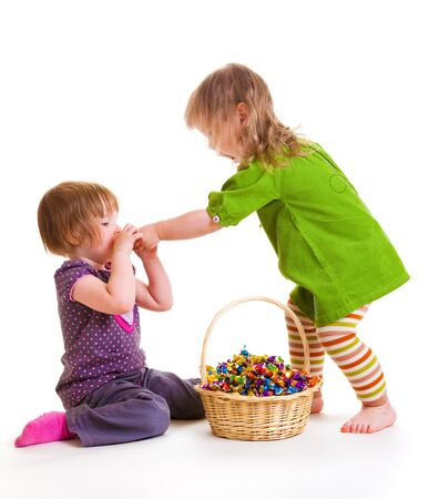 Two toddlers eating sweets from the wicker basket beside photo