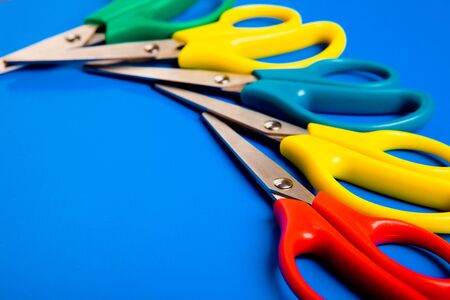Colorful scissors lying on blue cardboard background Stock Photo - 7021057