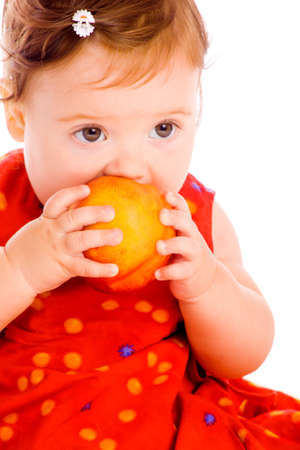 Portrait of a baby girl eating peach photo