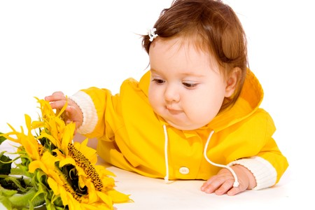 Beautiful baby girl in yellow  looking at sunflowers photo