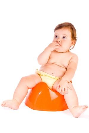 Frightened  baby sitting on the orange potty photo