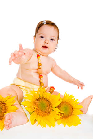 Baby girl with beads on, sunflowers lie beside photo