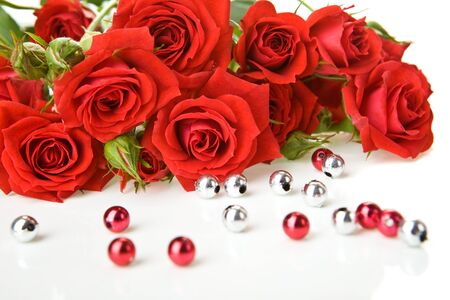 Red roses bouquet and beads on white background