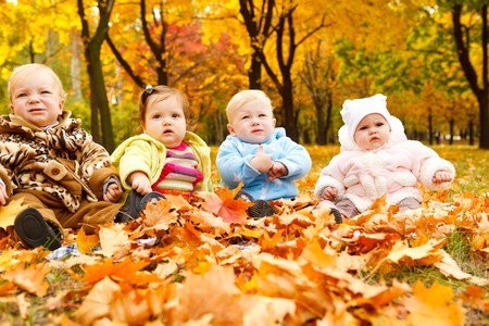 A group of cute babies having fun in the autumn park photo