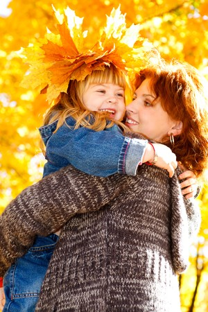 Happy  daughter embracing mother  in the autumn park photo