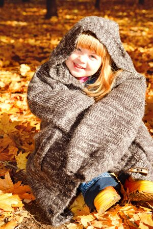 Lovely preschool girl sitting in an autumn park photo