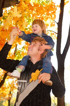 Happy autumn weekend for dad and his toddler daughter photo