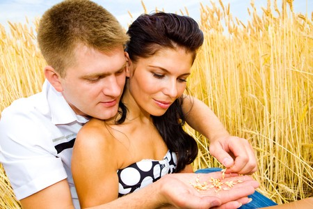 Man and woman holding wheat grain in hands photo