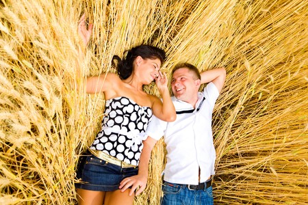 A loving happy couple lying in wheat photo