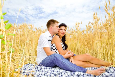 Romantic couple sitting in a wheat field photo