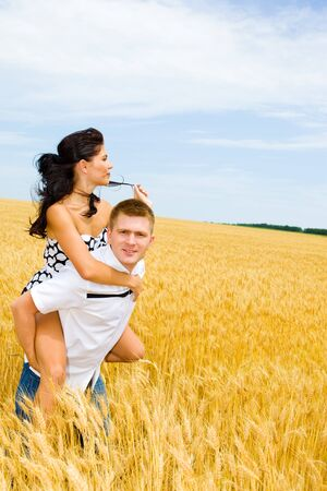 Young man and woman enjoying weekend in a wheat field photo