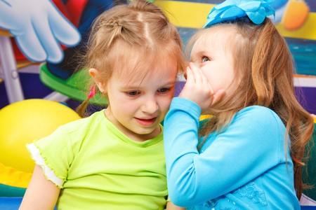 Preschool girl telling her friend some gossips photo