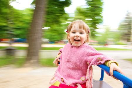 playground children: Happy girl having fun on the roundabout