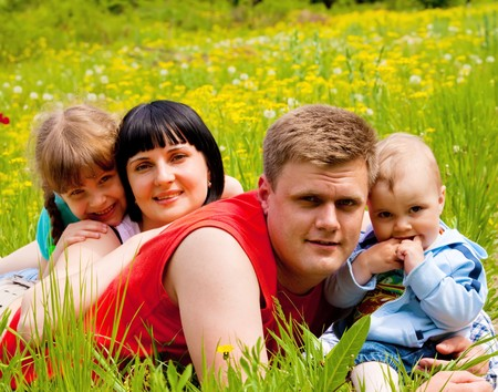 Beautiful happy family of four lying on the meadow Stock Photo - 7072682