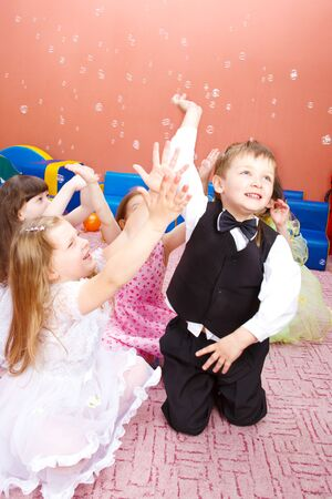 Group of cute preschool kids popping bubbles photo