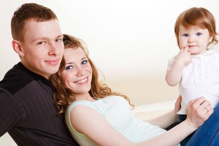 Young parents and their sweet baby, smiling photo