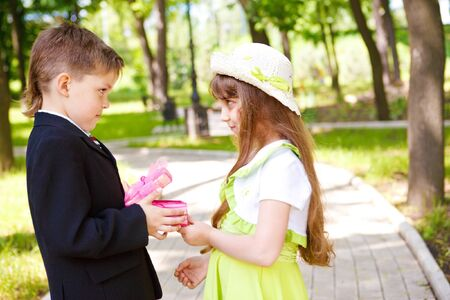 Preschool boy in suit giving a present box to the sweet girl photo