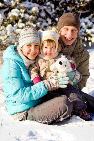 Happy attractive family playing in snow